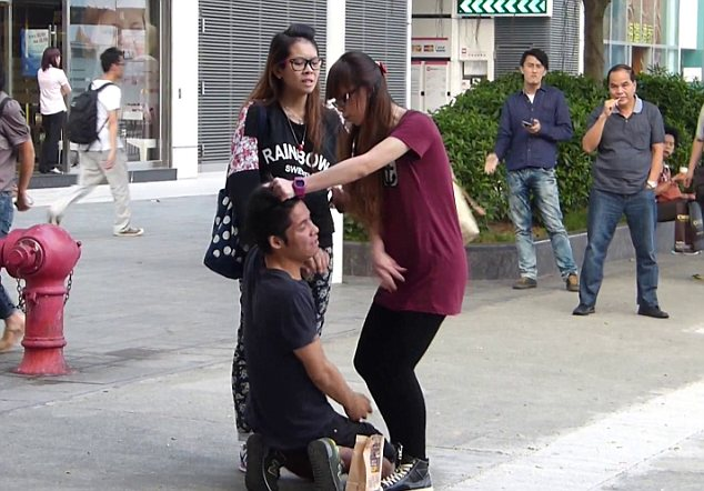 Pain: The man, named Chui, begged his girlfriend Cheng to stop hitting him as onlookers stood nearby