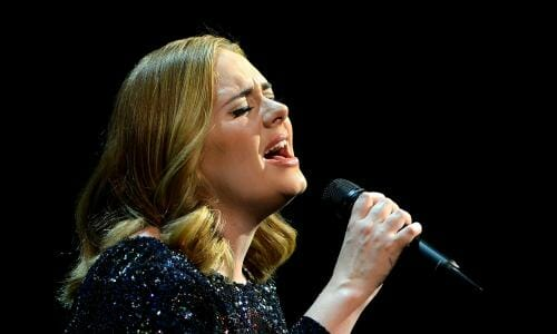 Adele singing with microphone in her hand