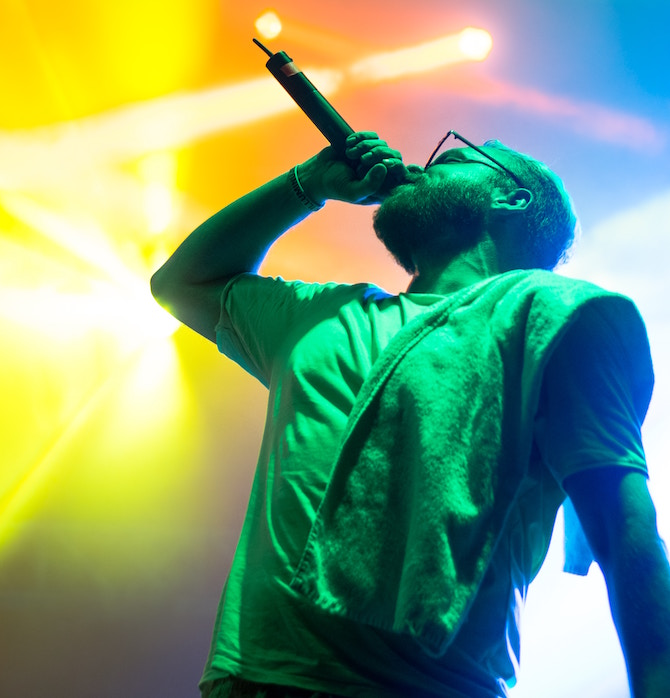 A singer in green and blue light holding a microphone to his mouth at an angle