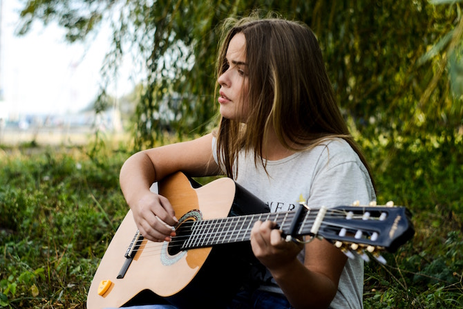 A young woman playing guitar and singing in a field